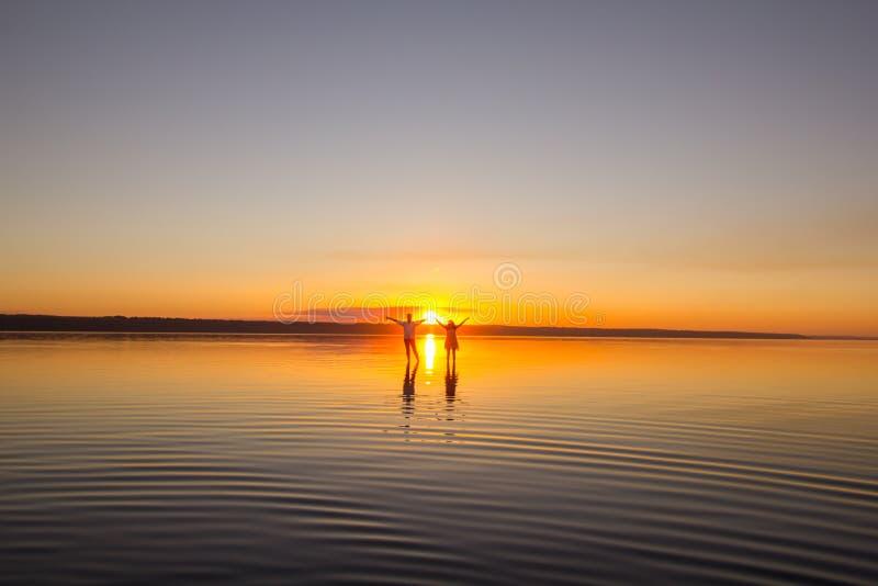Το νέο ζεύγος περπατά μακριά στο νερό στη θερινή παραλία Ηλιοβασίλεμα πέρα από τη θάλασσα Δύο σκιαγραφίες ενάντια στον ήλιο Ακριβ στοκ εικόνες