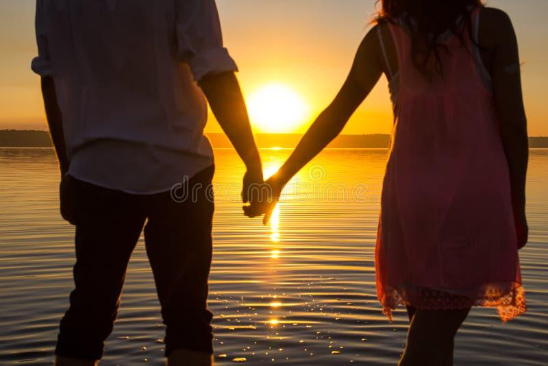 Το νέο ζεύγος περπατά στο νερό στη θερινή παραλία Ηλιοβασίλεμα πέρα από τη θάλασσα Δύο σκιαγραφίες ενάντια στον ήλιο Ακριβώς παντ στοκ εικόνες