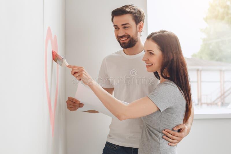 Το νέο ζεύγος που κάνει το διαμέρισμα επισκευάζει μαζί οι ίδιοι στοκ εικόνα