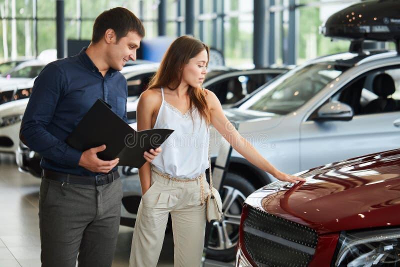 Το νέο ζεύγος στα κομψά ενδύματα θερινού χρόνου επιλέγει ένα νέο αυτοκίνητο στη εμπορία αυτοκινήτων στοκ εικόνα