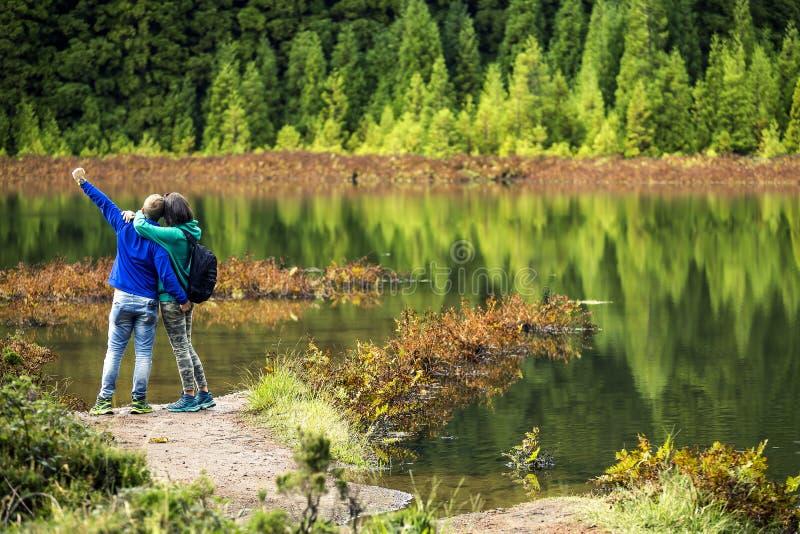 Το νέο ζεύγος στις ζωηρόχρωμες μπλούζες στέκεται μπροστά από την ηφαιστειακή λίμνη στοκ εικόνα