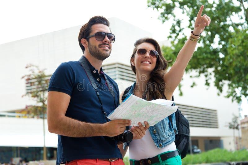 Το νέο ζεύγος τουριστών χρησιμοποιεί το χάρτη τους και υπόδειξη όπου θέλουν στοκ εικόνες