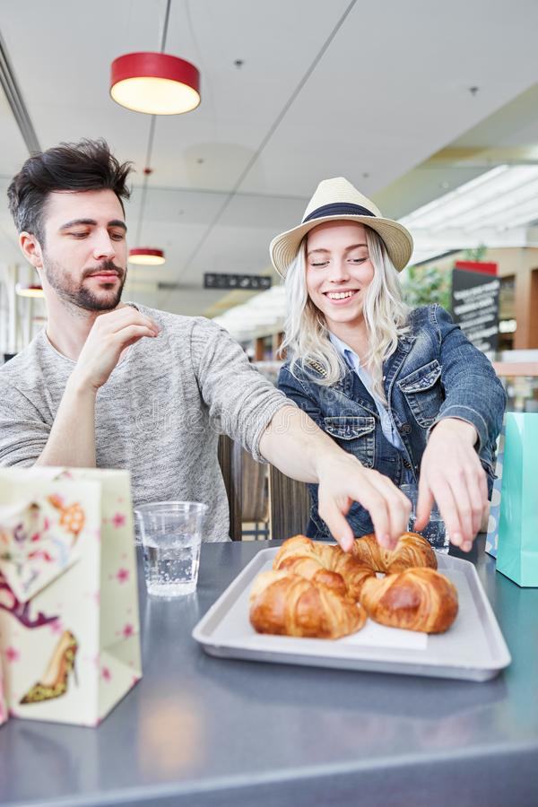 Το νέο ζεύγος τρώει croissants στο bistro στοκ εικόνα