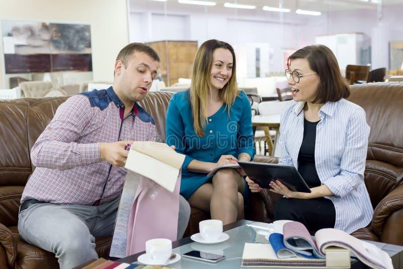 Το νέο ζεύγος των μικρών ιδιοκτητών επιχείρησης της συζήτησης καταστημάτων υφάσματος και συμβουλεύει τον αγοραστή στοκ εικόνες