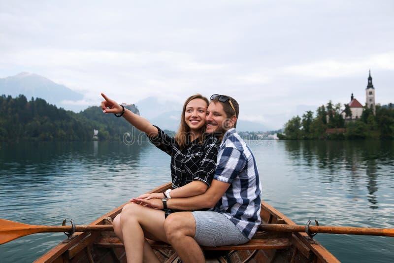 Το νέο ζεύγος των τουριστών στην ξύλινη βάρκα στη λίμνη αιμορράγησε, Σλοβενία στοκ εικόνα