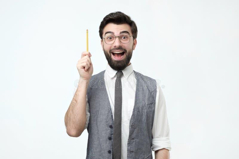 Το νέο ισπανικό άτομο με τη γενειάδα, τα γυαλιά και το μολύβι έχει μια καλή ιδέα στοκ εικόνα με δικαίωμα ελεύθερης χρήσης