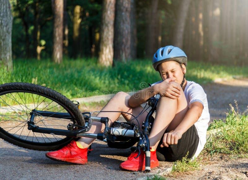 Το νέο καυκάσιο αγόρι στο κράνος και την άσπρη μπλούζα πήρε το ατύχημα και κάθεται στο έδαφος μετά από να πέσει από το ποδήλατο κ στοκ εικόνα με δικαίωμα ελεύθερης χρήσης