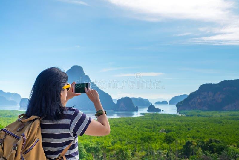 Το νέο κινητό τηλέφωνο χρήσης ταξιδιωτικών γυναικών backpacker παίρνει μια φωτογραφία όμορφου της φύσης ανατολής στην κορυφή της  στοκ φωτογραφία με δικαίωμα ελεύθερης χρήσης