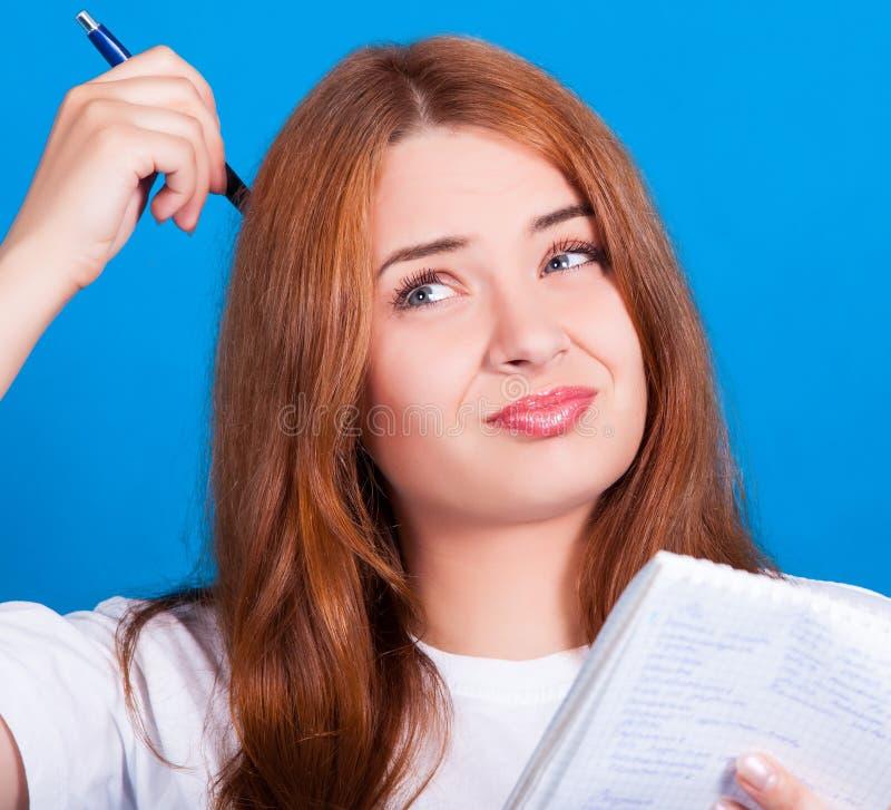 Το νέο κοκκινομάλλες κορίτσι με τα μπλε μάτια σε μια άσπρη μπλούζα σκέφτεται τι για να γράψει σε ένα σημειωματάριο στοκ φωτογραφία