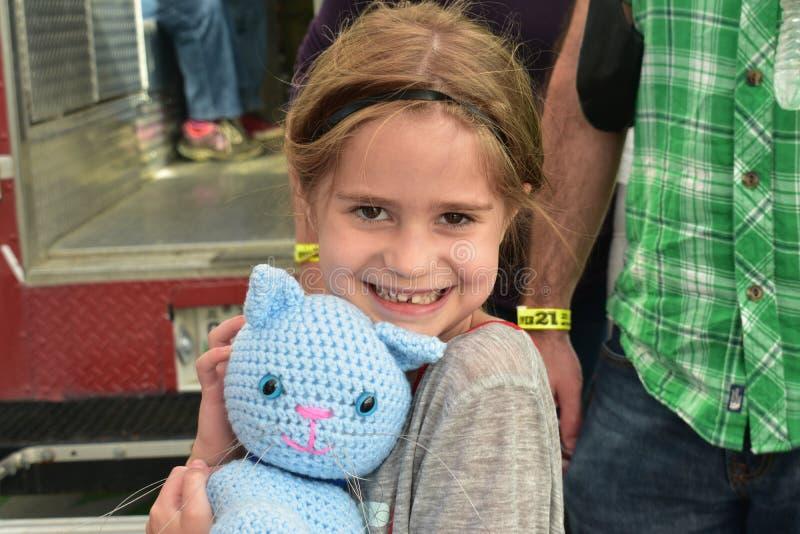 Το νέο κορίτσι αγκαλιάζει στοργικά τη γάτα τσιγγελακιών από τη διάσωση γατών του Νάσβιλ στο γεγονός Oktoberfest στοκ εικόνα