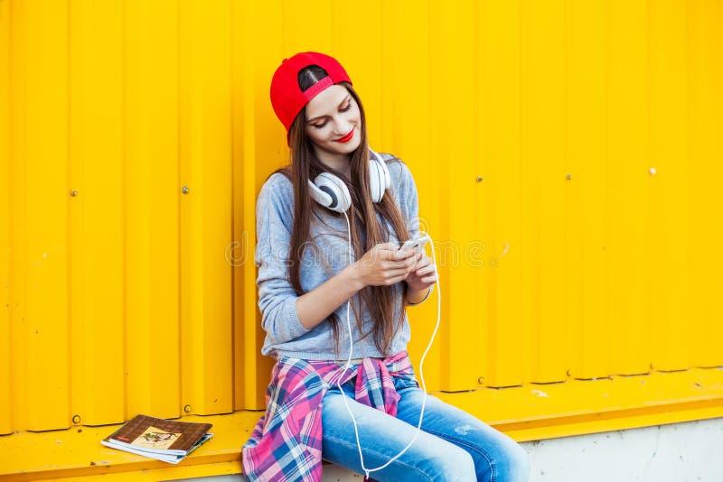 Το νέο κορίτσι ακούει τη μουσική στα άσπρα ακουστικά στοκ φωτογραφία με δικαίωμα ελεύθερης χρήσης