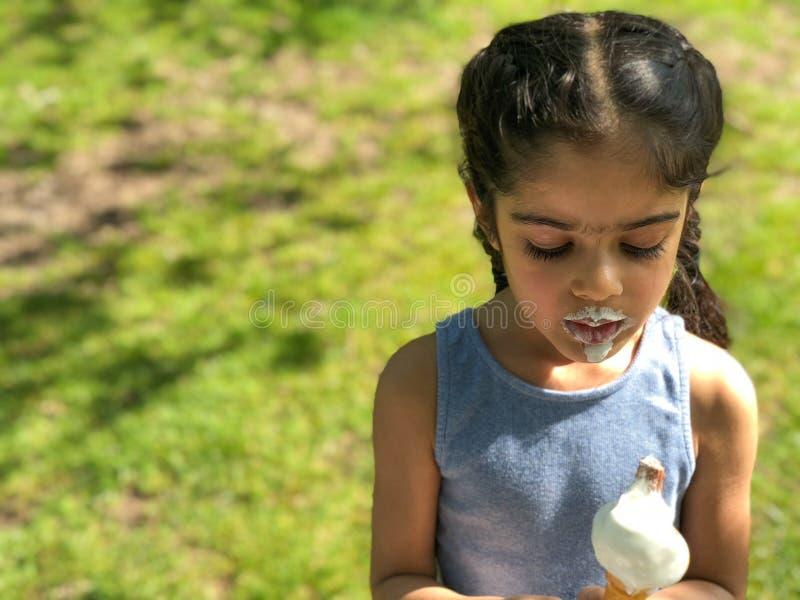 Το νέο κορίτσι απολαμβάνει το παγωτό της μια ηλιόλουστη ημέρα στοκ εικόνα