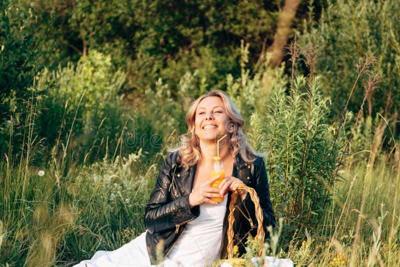 Το νέο κορίτσι κάθεται στο χορτοτάπητα Πιείτε το χυμό και το υπόλοιπο που είχαν ένα πικ-νίκ στοκ φωτογραφία με δικαίωμα ελεύθερης χρήσης