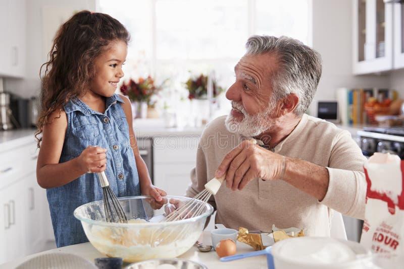 Το νέο κορίτσι και ο παππούς που κάνουν το μίγμα κέικ στον πίνακα κουζινών, που χαμογελά ο ένας στον άλλο, κλείνουν επάνω στοκ φωτογραφία με δικαίωμα ελεύθερης χρήσης