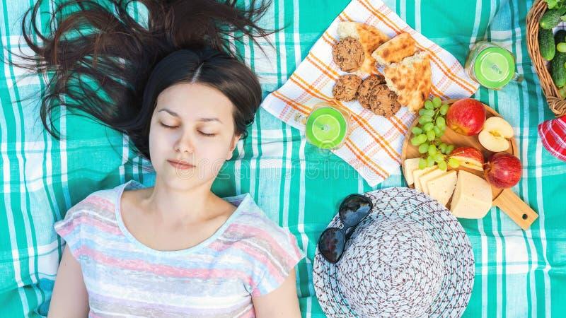 Το νέο κορίτσι με τη μακριά σκοτεινή τρίχα βρίσκεται σε ένα καρό σε ένα πικ-νίκ μια θερινή ημέρα - καλοκαιρινές διακοπές και έννο στοκ φωτογραφία