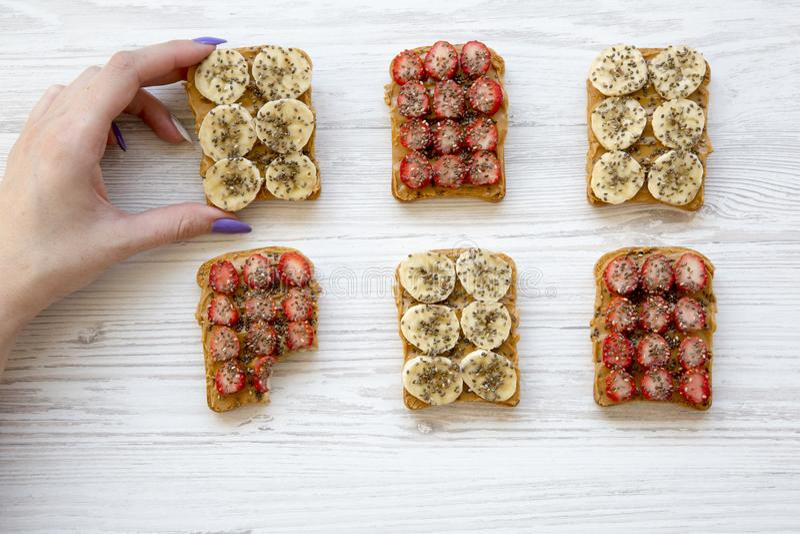 Το νέο κορίτσι παίρνει τη vegan φρυγανιά με τα φρούτα, σπόροι, φυστικοβούτυρο πέρα από το άσπρο ξύλινο υπόβαθρο, τοπ άποψη περίπο στοκ εικόνες
