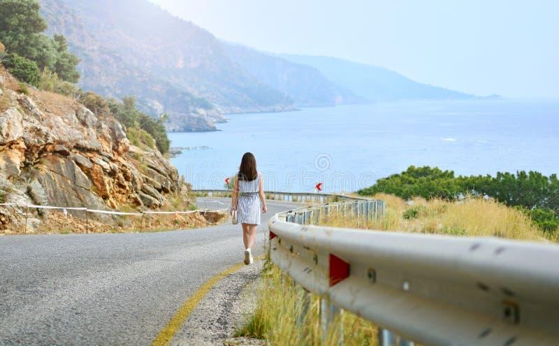 Το νέο κορίτσι πηγαίνει κάτω από το δρόμο βουνών στη θάλασσα στοκ φωτογραφία με δικαίωμα ελεύθερης χρήσης