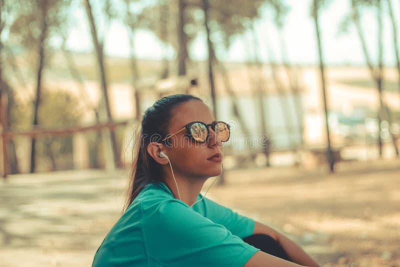 Το νέο κορίτσι που φορά τον αθλητισμό ντύνει τη μουσική ακούσματος στοκ φωτογραφίες με δικαίωμα ελεύθερης χρήσης