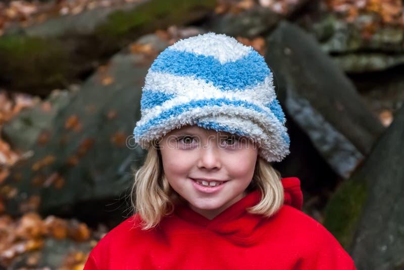 Το νέο κορίτσι που φορά το καπέλο εξετάζει τη κάμερα στοκ φωτογραφία