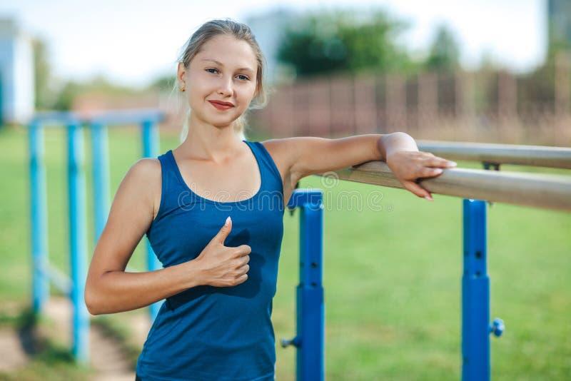 Το νέο κορίτσι σε ένα μπλε πουκάμισο και τις περικνημίδες στον υπαίθριο χώρο αθλήσεων το καλοκαίρι παρουσιάζει αντίχειρα, εξετάζο στοκ εικόνες με δικαίωμα ελεύθερης χρήσης