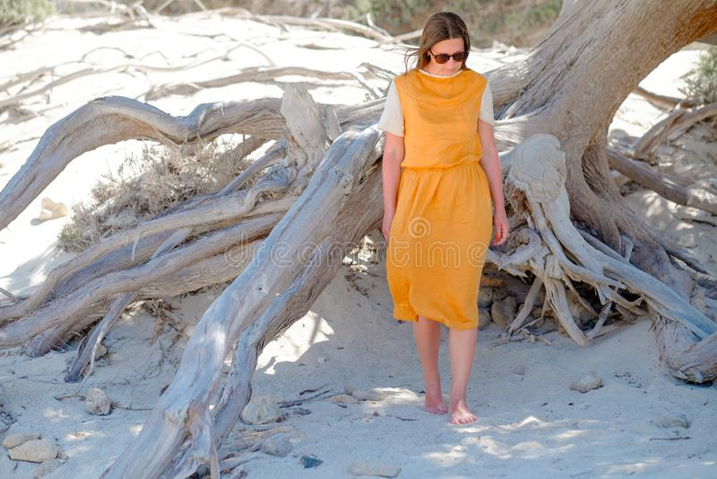 Το νέο κορίτσι σε ένα φόρεμα στέκεται χωρίς παπούτσια στην άσπρη άμμο κοντά στο δέντρο στοκ φωτογραφίες