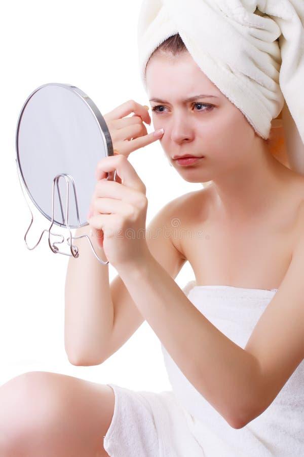 Το νέο κορίτσι σε μια πετσέτα στο κεφάλι του, βλέπει το πρόσωπό του στον καθρέφτη στοκ φωτογραφία