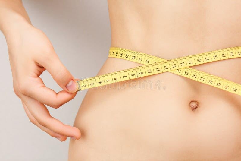 Το νέο κορίτσι σε μια φούστα μετρά τη μέση, έλεγχος βάρους στοκ εικόνες