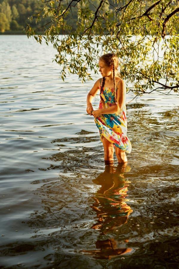 Το νέο κορίτσι στέκεται γόνατο-βαθιά στο νερό ενός ποταμού και συμπιέζει ένα υγρό φόρεμα στοκ εικόνα