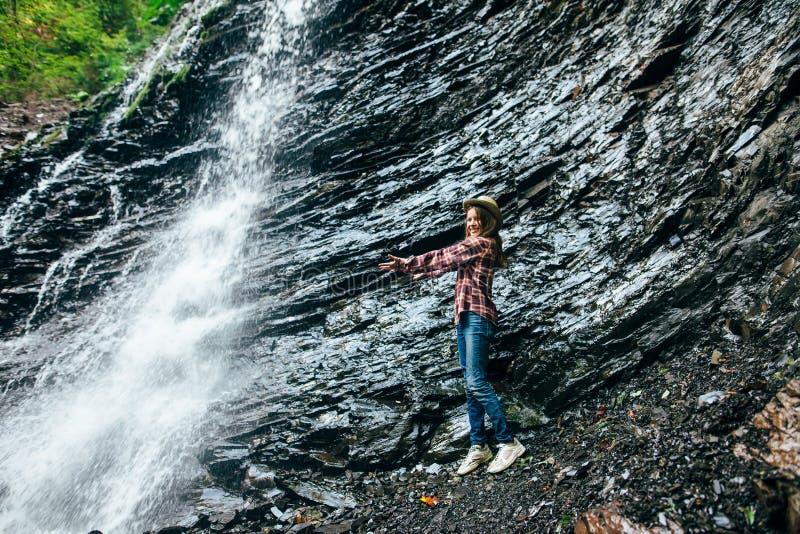 Το νέο κορίτσι στέκεται κοντά στον καταρράκτη και άντεξε τα όπλα σε τον στοκ εικόνες