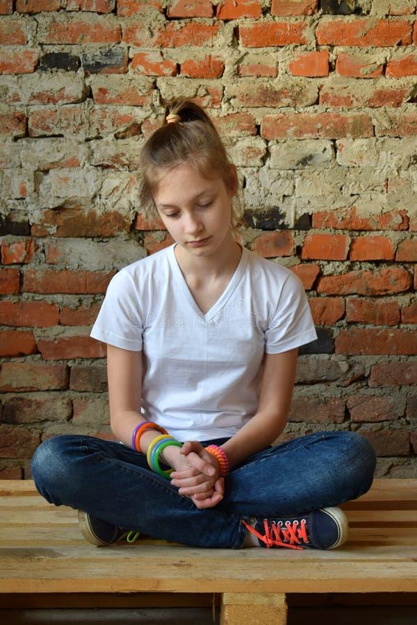 Το νέο κορίτσι στα τζιν και την άσπρη μπλούζα κάθεται στο πάτωμα και λυπημένος Έννοια ενός μη ευτυχούς εφήβου στοκ εικόνες με δικαίωμα ελεύθερης χρήσης