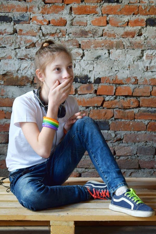 Το νέο κορίτσι στα τζιν και την άσπρη μπλούζα κάθεται στο πάτωμα και κλειστός παραδώστε το στόμα του, έκπληξη Πορτρέτο έννοιας το στοκ φωτογραφίες με δικαίωμα ελεύθερης χρήσης