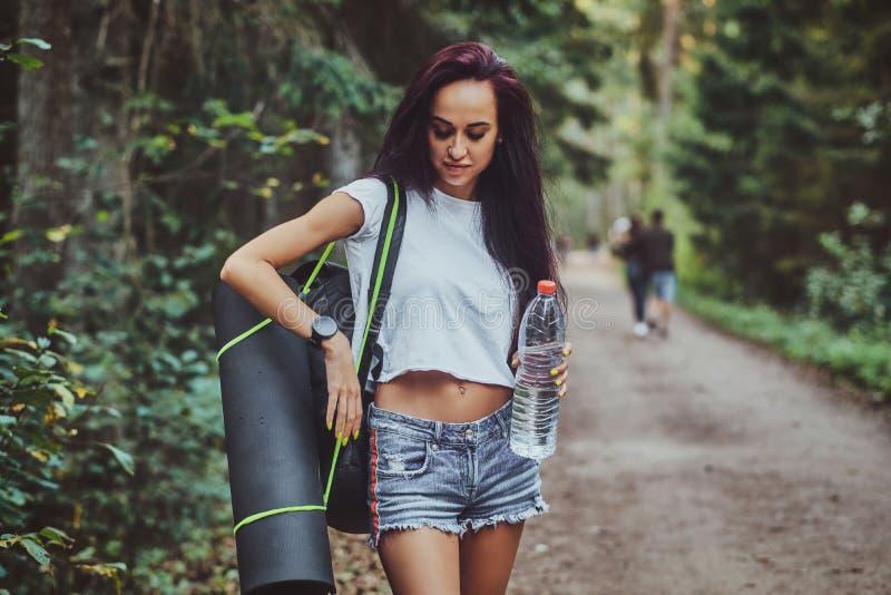 Το νέο κορίτσι στο δάσος δίνοντας το μπουκάλι νερό στοκ φωτογραφία με δικαίωμα ελεύθερης χρήσης