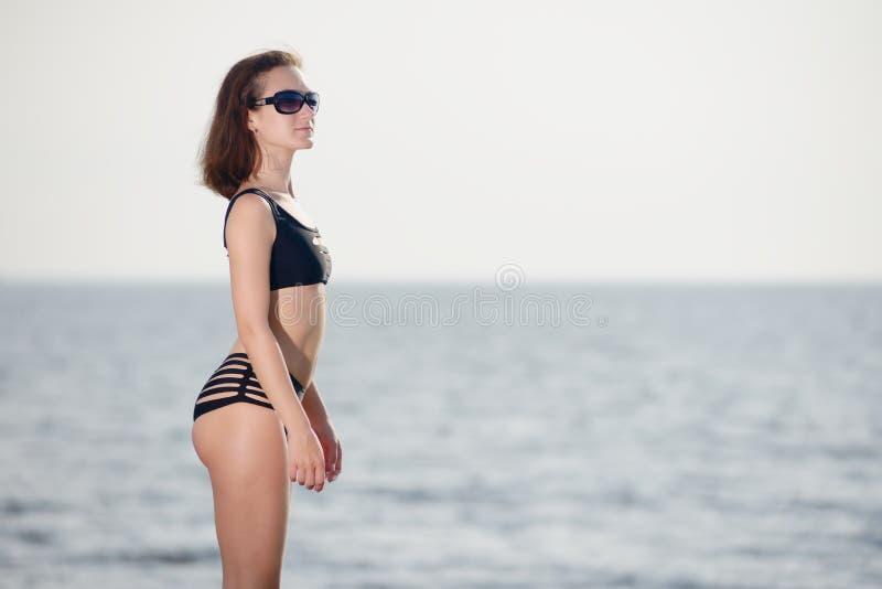 Το νέο κορίτσι στο μαύρο μπικίνι θέτει στην παραλία στοκ εικόνα