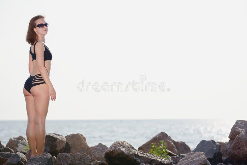 Το νέο κορίτσι στο μαύρο μπικίνι θέτει στην παραλία στοκ φωτογραφία με δικαίωμα ελεύθερης χρήσης
