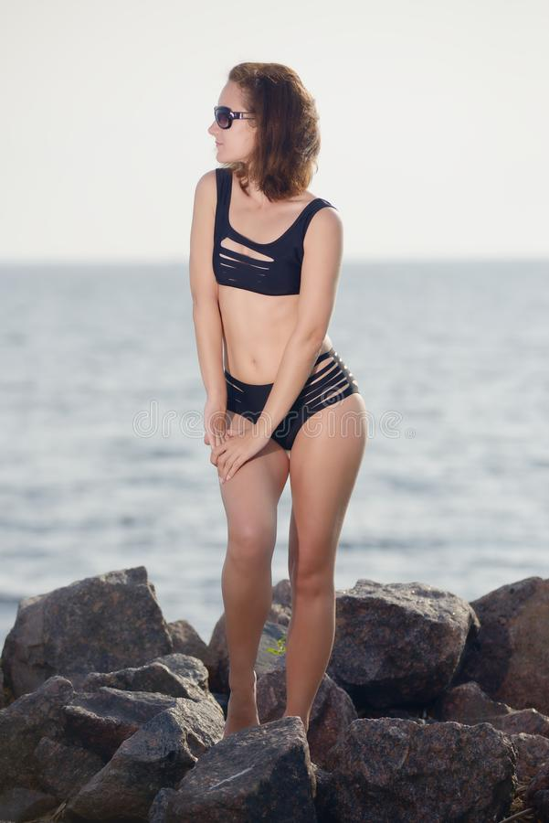 Το νέο κορίτσι στο μαύρο μπικίνι θέτει στην παραλία στοκ εικόνες