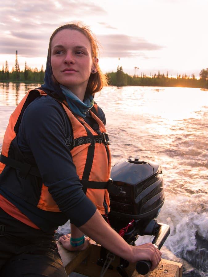 Το νέο κορίτσι στο σακάκι ζωής οδηγεί τη βάρκα με μια μηχανή στοκ φωτογραφίες με δικαίωμα ελεύθερης χρήσης