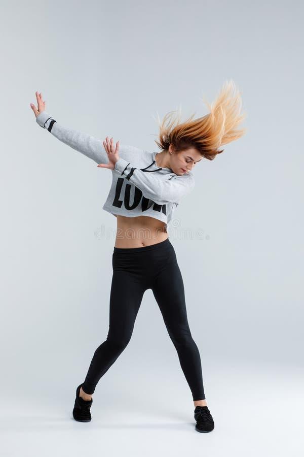 Το νέο κορίτσι, σύγχρονος χορευτής, παρουσιάζει ένα στοιχείο από το χορό, στην κίνηση, που απομονώνεται στο άσπρο υπόβαθρο στοκ φωτογραφία
