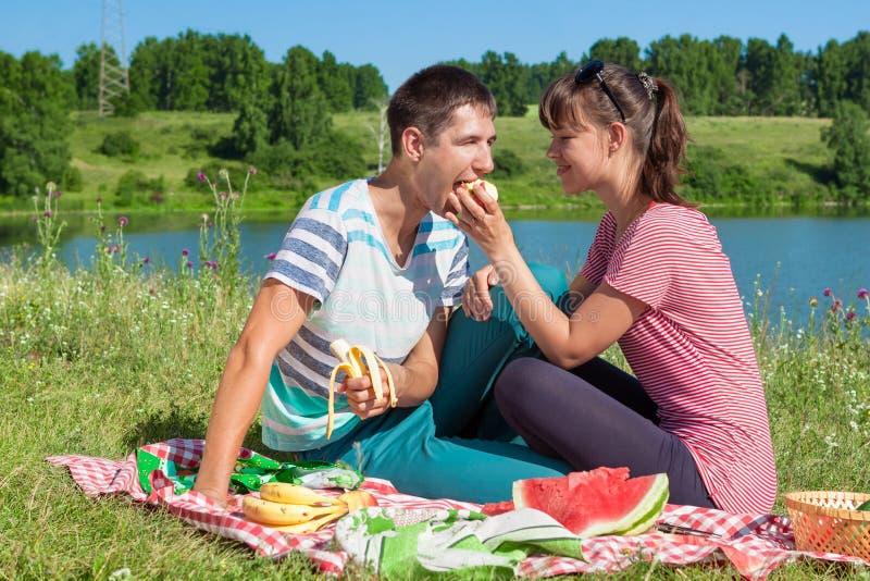 Το νέο κορίτσι ταΐζει ένα άτομο σε ένα πικ-νίκ στη λίμνη στοκ φωτογραφία