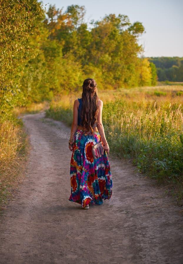 Το νέο κορίτσι χίπηδων boho πηγαίνει μακριά από το βρώμικο δρόμο στον τομέα απομονωμένο οπισθοσκόπο λευκό Υπαίθριο πορτρέτο στο χ στοκ φωτογραφίες με δικαίωμα ελεύθερης χρήσης