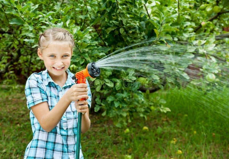 Το νέο κορίτσι χύνει το νερό από τη μάνικα στοκ φωτογραφίες