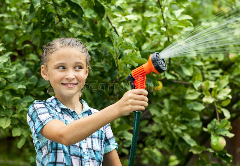 Το νέο κορίτσι χύνει το νερό από τη μάνικα στοκ εικόνα με δικαίωμα ελεύθερης χρήσης