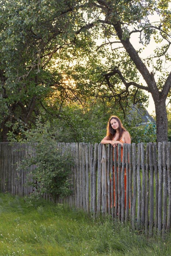 Το νέο κορίτσι brunette με μακρυμάλλη σε ένα αναδρομικό sarafan φόρεμα στέκεται κοντά σε έναν αγροτικό φράκτη στην επαρχία στο ηλ στοκ εικόνες