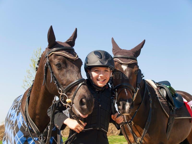 Το νέο κορίτσι Smilling ευτυχές μετά από κερδίζει το showjumping ανταγωνισμό με δύο άλογά της στοκ φωτογραφία με δικαίωμα ελεύθερης χρήσης