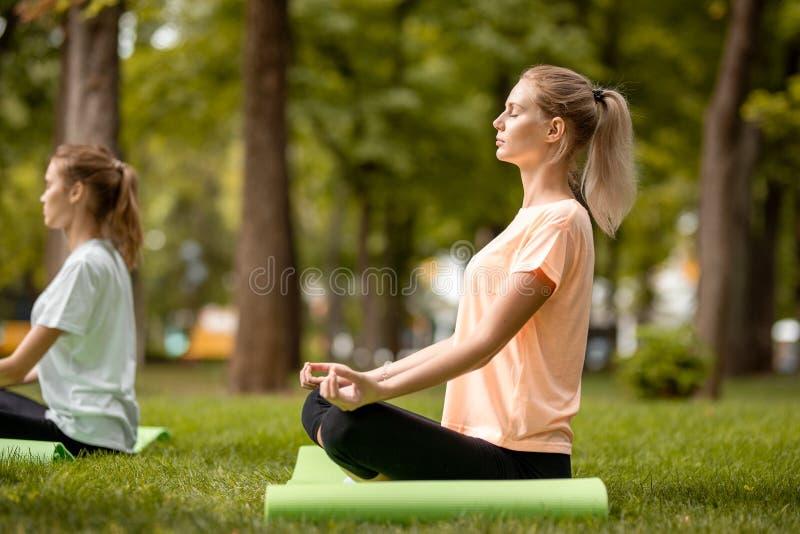 Το νέο λεπτό κορίτσι κάθεται στη θέση λωτού με το κλείσιμο των ματιών που κάνουν τις ασκήσεις με άλλα κορίτσια στην πράσινη χλόη στοκ εικόνα με δικαίωμα ελεύθερης χρήσης