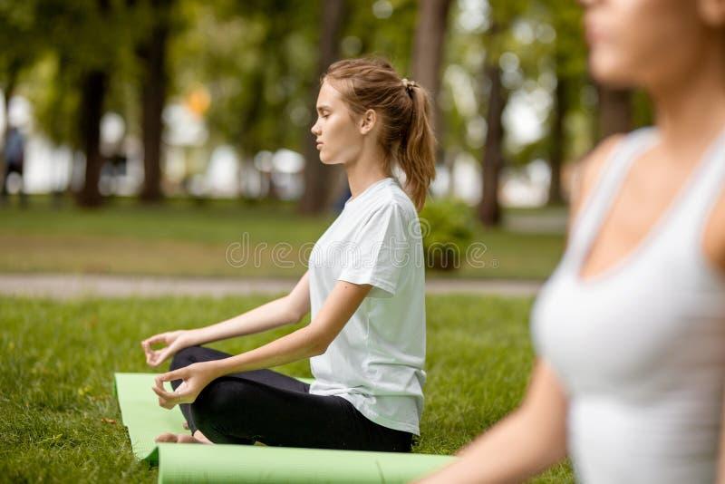Το νέο λεπτό κορίτσι κάθεται στη θέση λωτού με το κλείσιμο των ματιών που κάνουν τις ασκήσεις με άλλα κορίτσια στην πράσινη χλόη  στοκ εικόνες