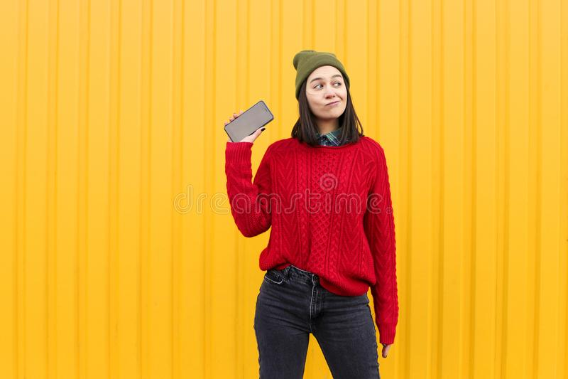 Το νέο μοντέρνο κορίτσι hipster που έχει τη διασκέδαση και που κάνει μορφάζει κοντά στο φωτεινό κίτρινο αστικό τοίχο τη νύχτα με  στοκ εικόνα