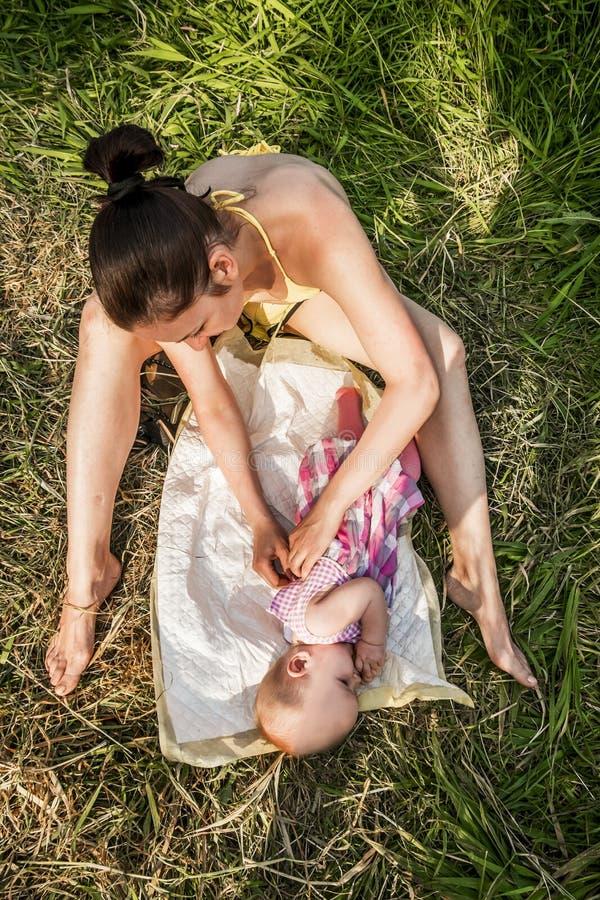 Το νέο μωρό μητέρων swaddles υπαίθρια μια θερινή ημέρα στοκ εικόνα