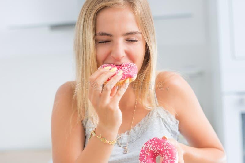 Το νέο ξανθό κορίτσι τρώει τα ρόδινα donuts στην εγχώρια κουζίνα με τις συγκινήσεις γούστου στοκ εικόνα
