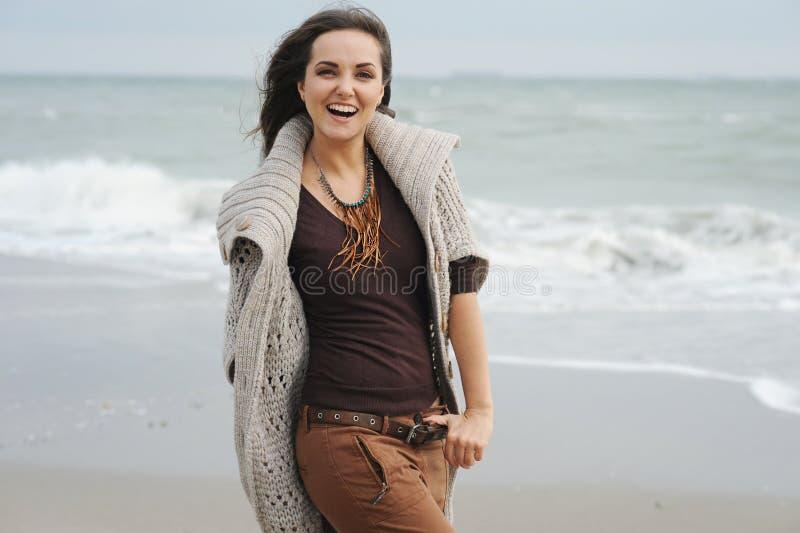 Το νέο περπάτημα γυναικών χαμόγελου από μια παραλία θάλασσας, μόδα φθινοπώρου, θεραπεύει στοκ φωτογραφία