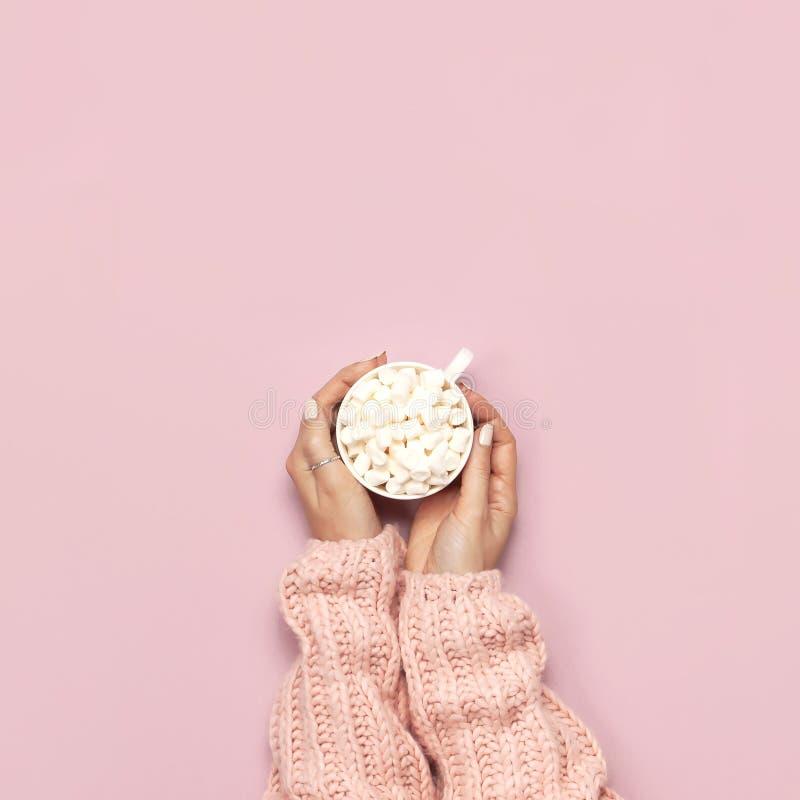 Το νέο ποτό έτους Χριστουγέννων, άσπρη κούπα με marshmallows στο θηλυκό παραδίδει τον πλεκτό κάλαμο πουλόβερ και καραμελών στη ρό στοκ εικόνες